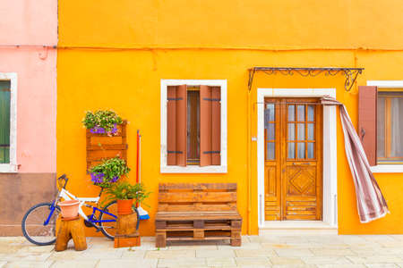 Yellow house with flowers, bench and a bicycle. Colorful houses in Burano island near Venice, Italy. Venice postcard. Famous place for european tourism and travel.
