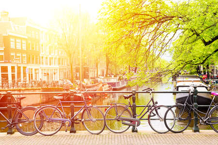 Bicycles on the bridge in Amsterdam, Netherlands against a canal with a sunlight. Amsterdam postcard. Tourism concept