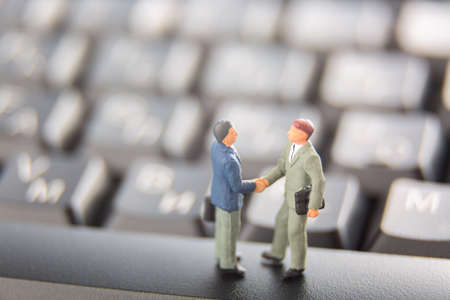 Business deal or agreement and success concept. Two miniature businessmen shaking hands while standing on the keys of a black keyboard