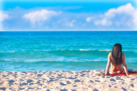 Summer vacation, tourism and relax concept. Woman in swimming suit from back sitting on exotic beach. Idyllic background