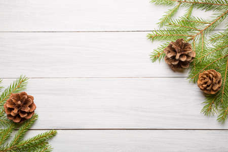 Christmas white wooden background with fir tree branches and cones. Top view with copy space for your text.