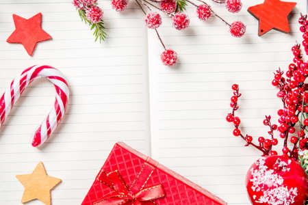 Christmas decorations, candy cane, frozen red berries, stars and gift box frame on notebook, copy space for text. Can be used for Christmas or new year project. Wishing to Santa Claus concept