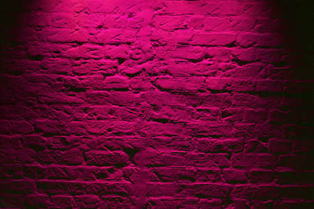 Grunge neon pink brick wall texture background. Magenta colored brick wall texture architecture pattern
