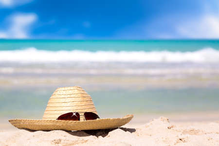 Beach accessories on sand for summer vacation concept. Straw hat with sunglasses on white sand against turquoise water amazing ocean and blue sky in the background