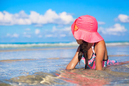 Vacation concept. Young girl with pink hat in blue water ocean