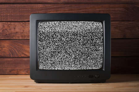 Old vintage TV set televisor on wooden table againt dark wooden wall background with no signal television grainy noise effect on the screen.