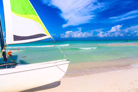 Tropical beach with a colorful sailboat on a summer day with turquoise water and blue sky. Varadero resort, Cuba