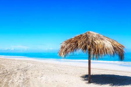 Straw umbrella on empty seaside beach in Varadero, Cuba. Relaxation, vacation idyllic background Stockfoto