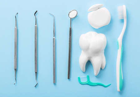 Dental health and teethcare concept. Professional steel dental instruments with a mirror near white tooth model, toothbrush and dental floss on light blue background Banco de Imagens