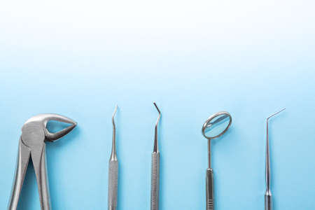 Dental health and teethcare concept. Top view of dental tools set on blue background in dentists clinic: dental mirror, explorers, forceps. Free space for your text. 写真素材