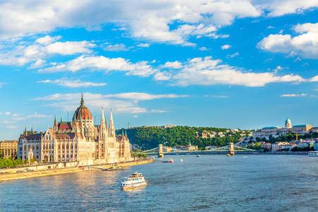 Parliament and riverside in Budapest Hungary with sightseeing ships during summer sunny day with blue sky and clouds. Travel and european tourism concept