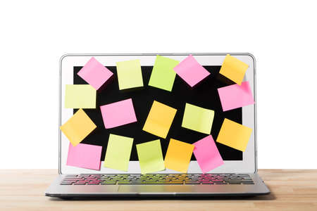 Many blank sticky notes covering a laptop screen on wooden table against isolated white background. Concept of deadlines or ideas