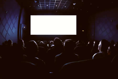 Persone al cinema che guardano un film. Schermo bianco vuoto vuoto.