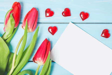 Colorful spring tulip flowers with blank photo and decorative red hearts on light blue wooden background as greeting card. Mothersday, love or spring concept Stock Photo