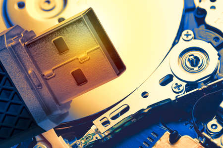 Toned image of USB memory stick against hard disk drive plate background. Technology concept Archivio Fotografico
