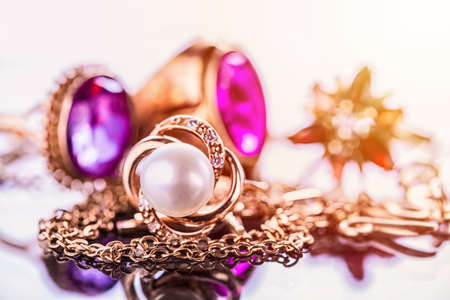 Elegant luxury composition of gold jewelry with pearl ring, amethysts and rubys gemstones on light background close-up macro and reflection Foto de archivo