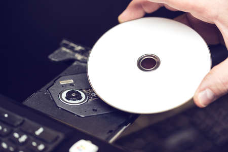 Male hand inserting a DVD into a disk drive. Software or drivers installation concept