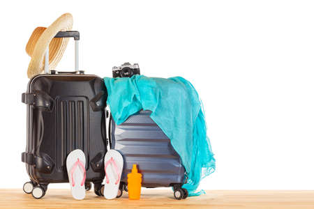 Summer holidays concept. Suitcases baggage with straw hat, blue pareo, flip flops, sunscreen lotion bottle and retro camera against white isolated background. Image for tourism and vacation mockup