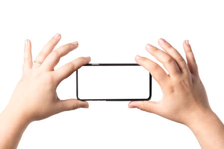 Female hands holding mobile smart phone isolated on white background. Blank white screen. Concept of selfie making photo.
