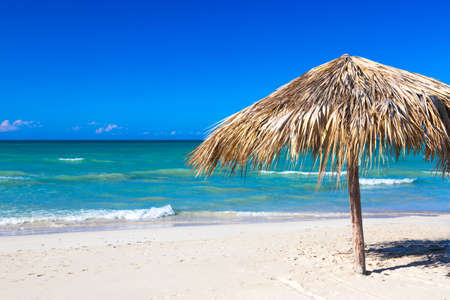 Straw umbrella on empty seaside beach in Varadero, Cuba. Relaxation, vacation idyllic background Standard-Bild