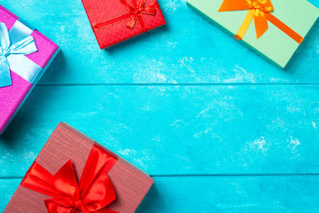 Colorful gift boxes with ribbons on nice blue wooden background. Copy space. Christmas or birthday celebration holiday theme Banco de Imagens
