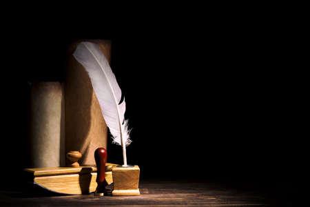 Concepto de literatura y poesía. Tintero antiguo con pluma, papel secante, sello cerca de pergaminos contra fondo negro. Luz dramática y espacio libre. Bodegón vintage