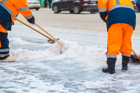 Communal services workers sweep snow from road in winter, Cleaning city streets and roads after snow storm. Moscow, Russia