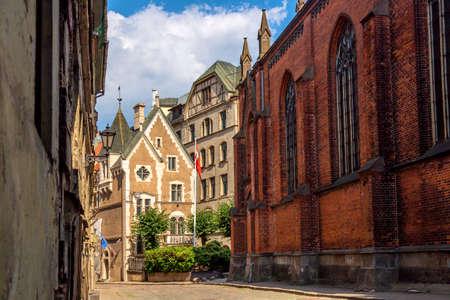 Narrow cobblestone street in old town of Riga city, Latvia. Summer sunny day Stock Photo