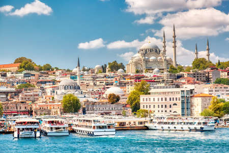 Touristic sightseeing ships in Golden Horn bay of Istanbul and view on Suleymaniye mosque with Sultanahmet district against blue sky and clouds. Istanbul, Turkey during sunny summer day