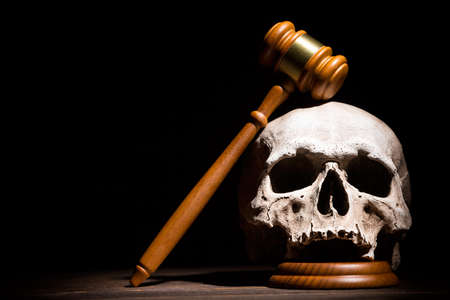 Legal law, justice and murderment concept. Wooden judge gavel hammer on human skull against black background. Free space