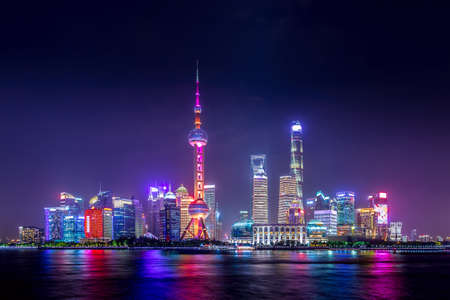 Cityscape of Shanghai at twilight sunset. Panoramic view of Pudong business district skyline from the Bund Фото со стока