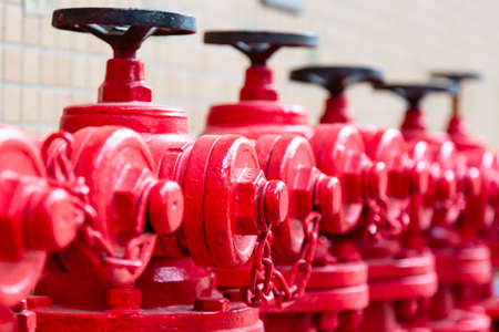 A line of red fire hydrants in Guangzhou, China Фото со стока