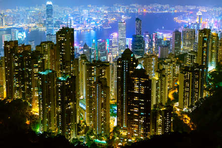 The most famous view of Hong Kong at twilight sunset. Hong Kong skyscrapers skyline cityscape view from Victoria Peak illuminated in the evening. Hong Kong, special administrative region in China