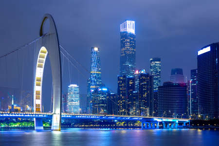 Guangzhou cityscape over the Pearl River with Liede Bridge and financial district illuminated in the evening. Guangzhou, Southern China