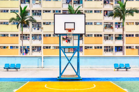Iconic shot of Hong Kong basketball court with palms and colorful estate building.