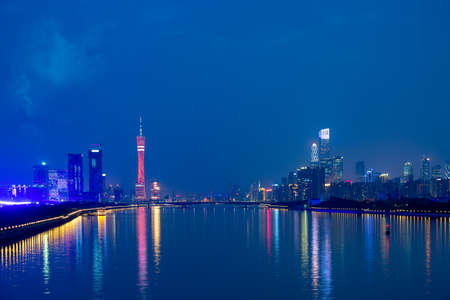 Guangzhou cityscape over the Pearl River with Liede Bridge, Canton TV Tower and financial district illuminated in the evening. Guangzhou, Southern China Фото со стока