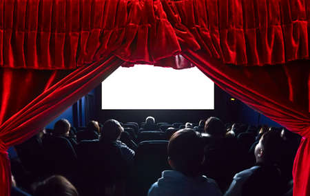 People in the cinema watching a movie. Blank empty white screen. Red theater curtain on the foreground. Фото со стока