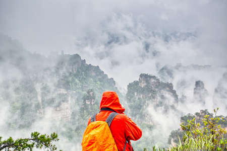 Zhangjiajie National park. Famous tourist attraction in Wulingyuan, Hunan, China. Amazing natural landscape with photographer in orange raincoat and stone pillars quartz mountains in fog and clouds. Фото со стока