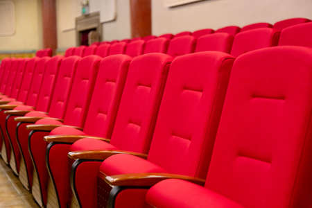 Red seats armchairs in theater in a row. Theater or conference room interior