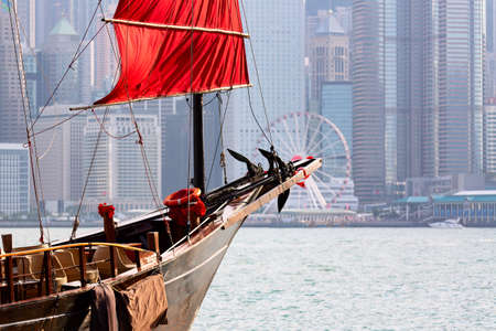 Old wooden tourist junk ferry boat in Victoria Harbor and famous Hong Kong island view with observation wheel