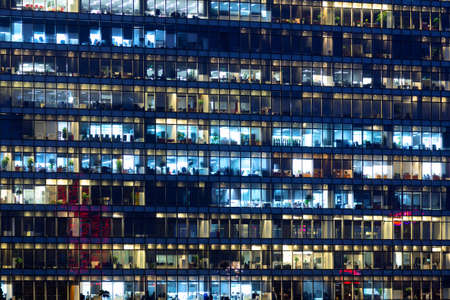 Office building exterior in the late evening with interior lights. Business people working in the evening. Illuminated office building. Фото со стока