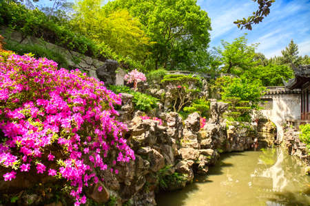 Pink flowers and details of the historic Yuyuan Garden during summer sunny day in Shanghai, China.