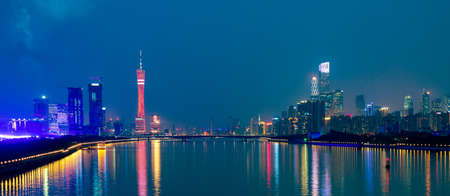 Guangzhou cityscape over the Pearl River with Liede Bridge, TV Tower and financial district illuminated in the evening. Guangzhou, Southern China