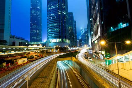 Straßenverkehr bei Sonnenuntergang in der Dämmerung in Hongkong. Bürohochhausgebäude und mit verschwommenen Autolichtspuren. Hongkong, Sonderverwaltungszone in China