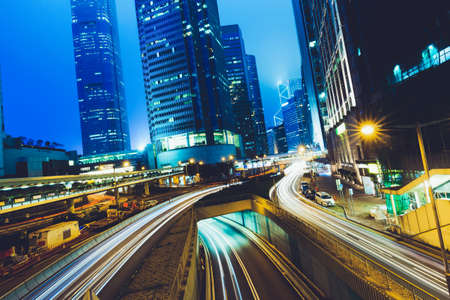 Street traffic at twilight sunset in Hong Kong. Office skyscraper buildings and with blurred car light trails. Hong Kong, Special administrative region in China. Toned.