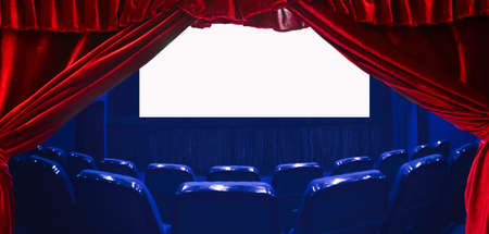 Empty cinema auditorium with empty white screen and red theater curtain on the foreground. Empty rows of theater or movie seats. Blue toned