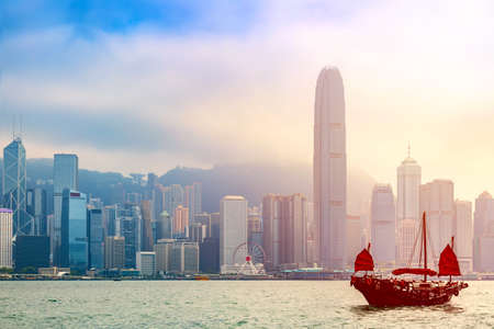 Old wooden tourist junk ferry boat in Victoria Harbor against famous Hong Kong island view with skyscrapers during sunrise.