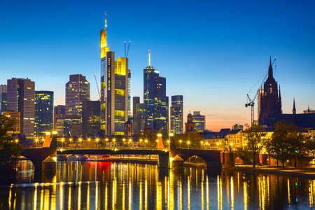 Panoramic view cityscape skyline of business district with skyscrapers and mirror reflections in the river Main during sunset blue hour, Frankfurt am Main. Hessen, Germany. 免版税图像