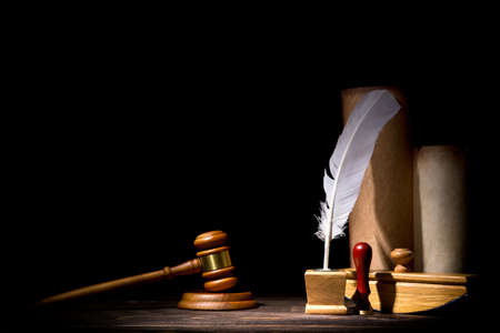 Wooden judge gavel hammer, old inkstand with feather quill, blotter, seal near scrolls against black background. Dramatic light. Vintage still life