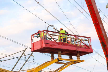 Electrical engineers repairing wire on electric power pole at a railway station.